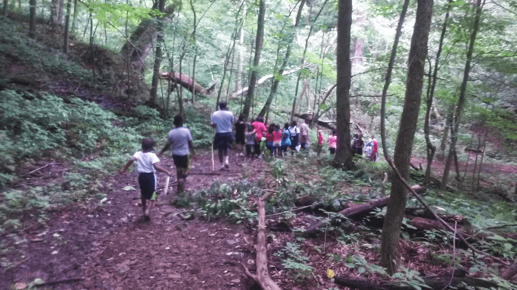 Children walking on a trail at camp.